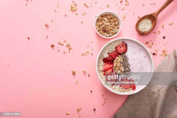 a bowl of healthy and delicious strawberry smoothie with grains and fresh fruit. - bowl stock pictures, royalty-free photos & images