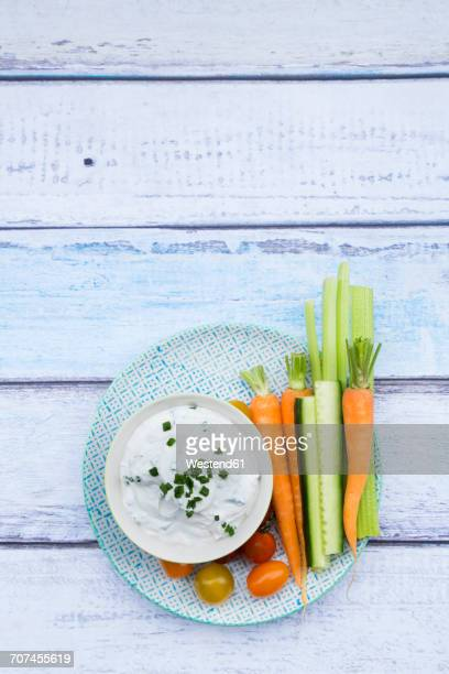 Bowl of herb yoghurt dip, cherry tomatoes and vegetable sticks on plate