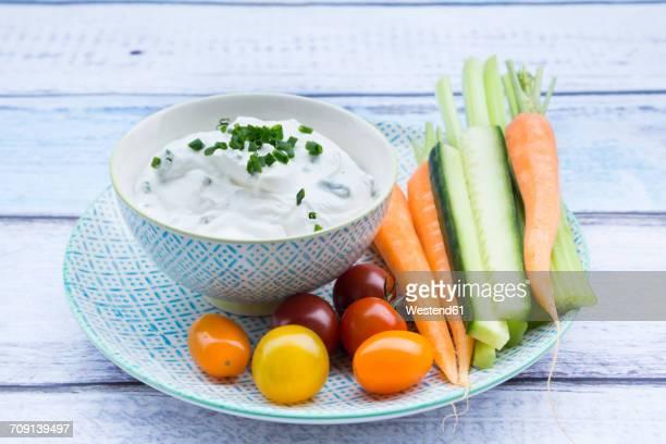 bowl of herb yoghurt dip, cherry tomatoes and vegetable sticks on plate - タレ ストックフォトと画像