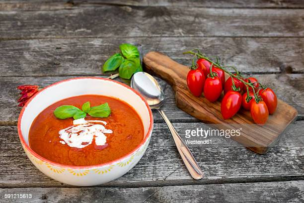 bowl of homemade tomato soup on wood - tomato soup stock photos and pictures