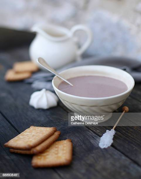 A bowl of hot chocolate and biscuits on wood table