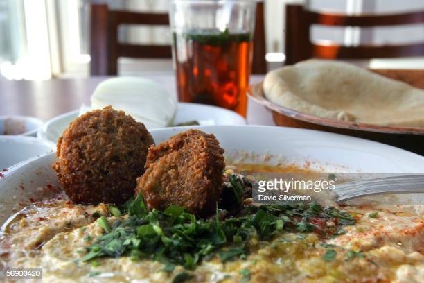 A bowl of hummous is served with olive oil falafel balls and sprinkled with chopped parsley alongside freshbaked pita bread and a glass of tea...