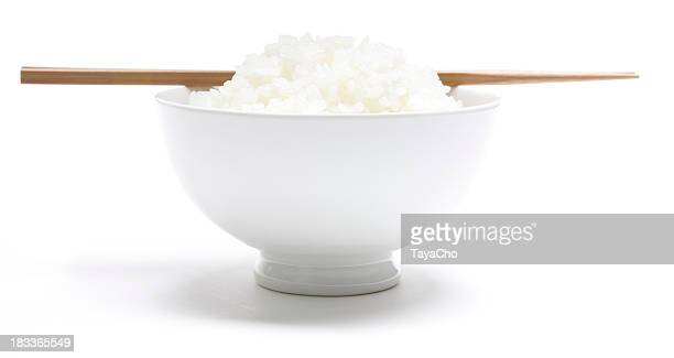 Bowl of Japanese rice with bamboo chopsticks resting on top