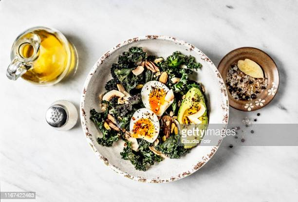 bowl of kale salad with boiled eggs and avocado on white background - salad stock pictures, royalty-free photos & images