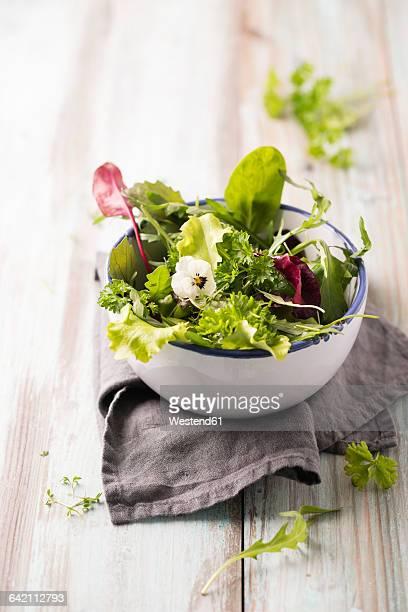 Bowl of leaf salad garnished with horned violet