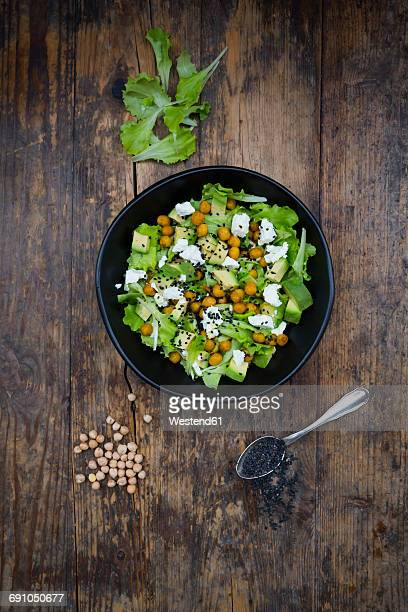 Bowl of leaf salad with roasted chick-peas, avocado, feta and black sesame