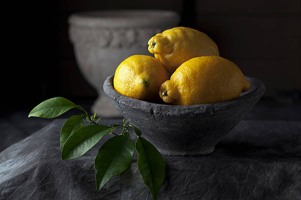 Bowl of lemons with leaves, close up