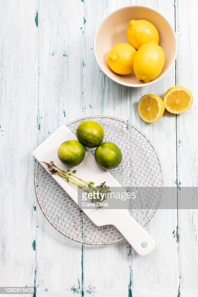 Bowl of lemons with limes on chopping board, still life, overhead view