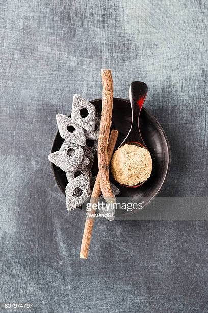 Bowl of licorice roots, licorice and spoon of licorice powder