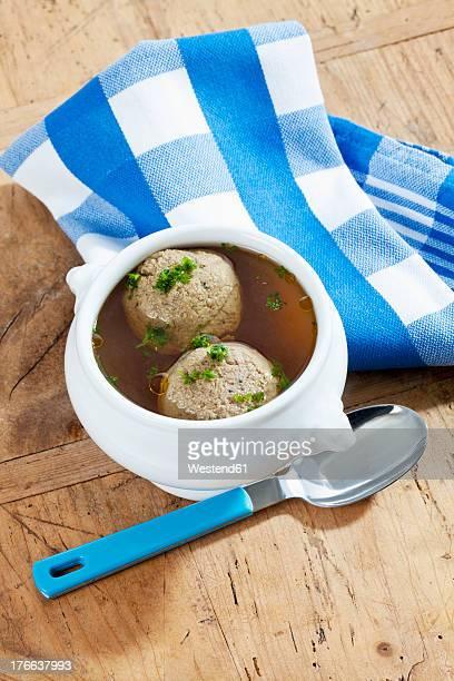 Bowl of liver dumplings soup on wooden table
