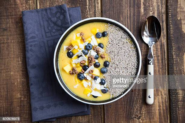 Bowl of mango smoothie with diced mango, coconut flakes, blueberries, choco crunch and chia