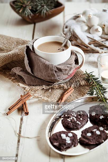 Bowl of Masala chai with almond milk and chocolate cinnamon cookies on wood