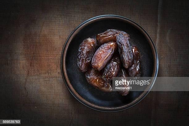 Bowl of Medjooll dates on wood