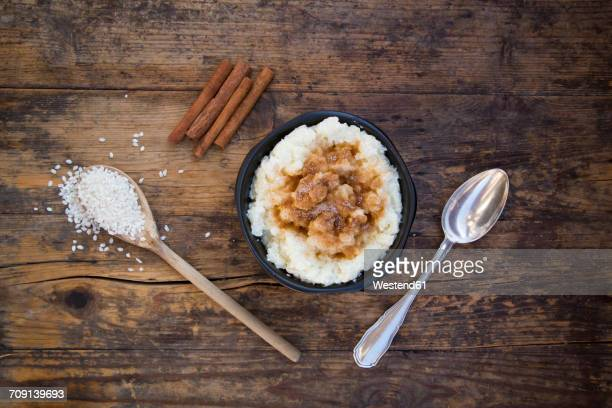 Bowl of milk rice pudding with cinnamon on wood