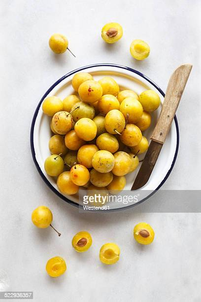 Bowl of mirabelles and a kitchen knife on white background