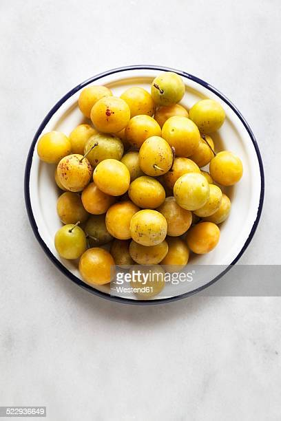 Bowl of mirabelles on white background