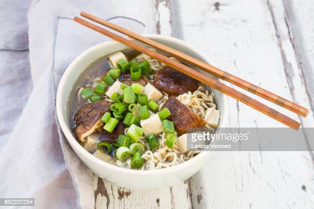 Bowl of miso ramen soup with organic tofu, shitake mushrooms and spring onions on wood