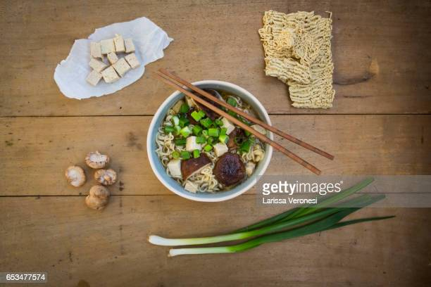 Bowl of miso ramen soup with organic tofu, shitake mushrooms and spring onions on dark wood