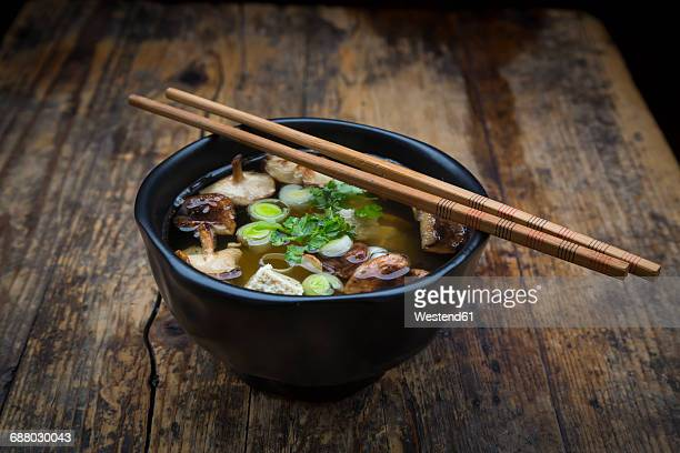 bowl of miso soup with organic tofu, shitake mushrooms, leek and parsley on dark wood - miso sauce stock pictures, royalty-free photos & images