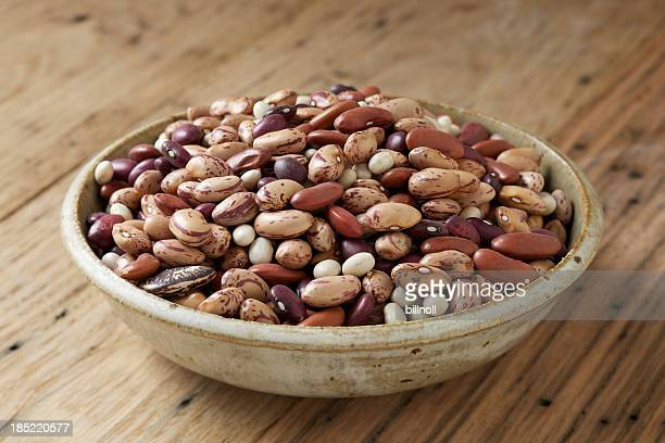 bowl of mixed dry beans on wood table - pinto bean stock pictures, royalty-free photos & images