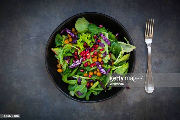 bowl of mixed leaf salad with pomegranate seed, red cabbage and roasted curcuma chick peas - green salad stock pictures, royalty-free photos & images