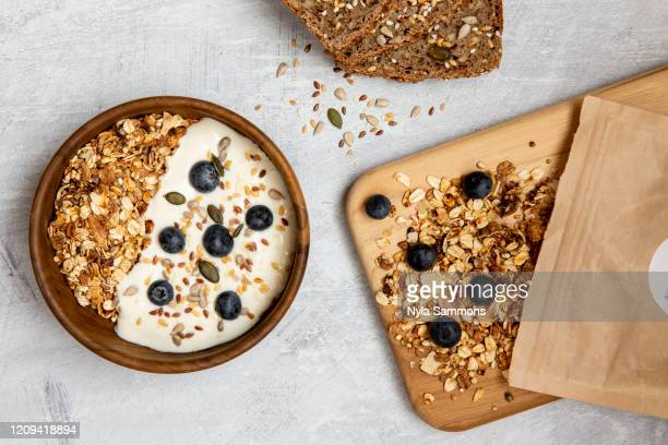bowl of muesli and blueberries on yogurt, multi-seed bread - granola stock pictures, royalty-free photos & images