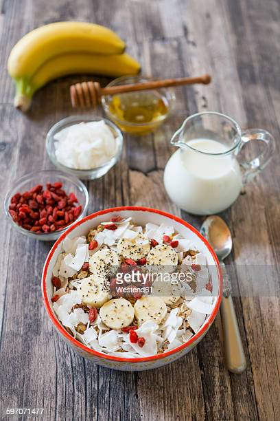 Bowl of muesli with banana slices, chia seeds, coconut chips and goji berries