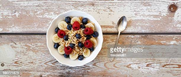 Bowl of muesli with banana slices, raspberries and blueberries
