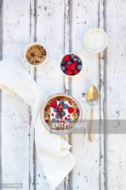 bowl of muesli with greek yogurt, popped quinoa, raspberries, blueberries and pomegranate seed - ティースプーン ストックフォトと画像