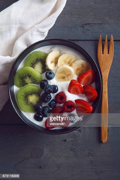 Bowl of natural yoghurt and different fresh fruits