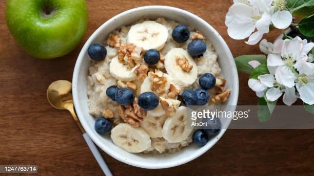 bowl of oatmeal porridge with banana, blueberry, walnuts - ポリッジ ストックフォトと画像