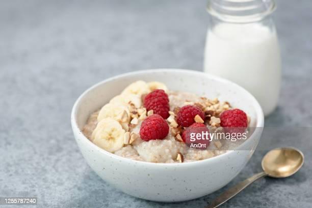 bowl of oatmeal porridge with raspberries and banana slices - ポリッジ ストックフォトと画像
