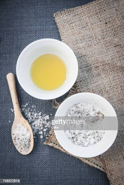 Bowl of oil and salt mixed with herbs, ingredients for home-made body scrub, overhead view