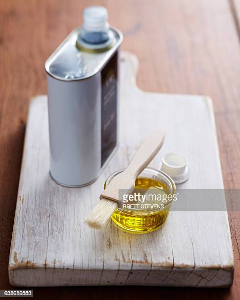 Bowl of olive oil and pastry brush on wooden chopping board