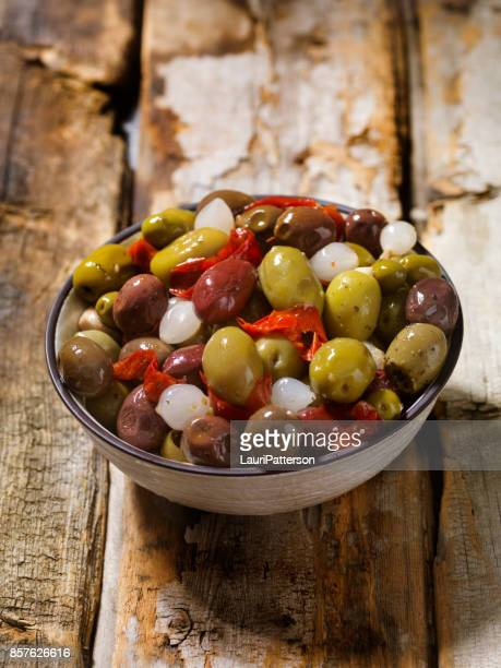 bowl of olives with pearl onions and peppers - green olive stock photos and pictures
