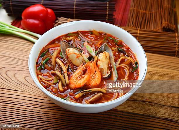 ボウルのオレンジのスープに麺とシーフード - 韓国文化 ストックフォトと画像