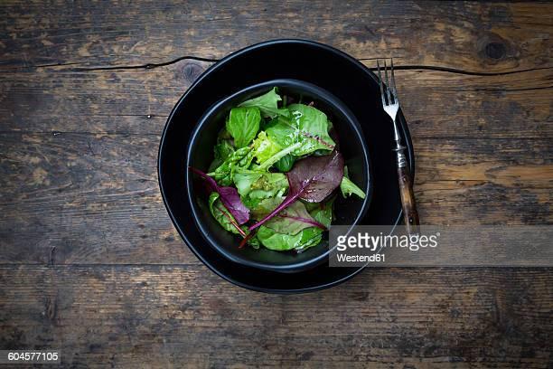 Bowl of organic mixed salad on dark wood