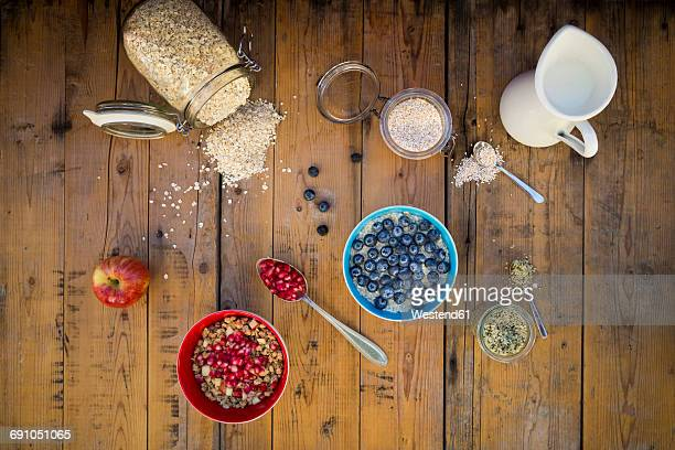 Bowl of overnight oats with blueberries and bowl of granola with pomegranate seed and red apple on wood