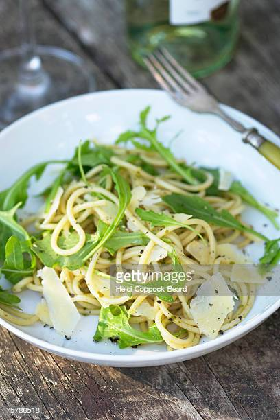 bowl of pasta with parmeasan cheese and rocket, wineglass and bottle - heidi coppock beard stock-fotos und bilder