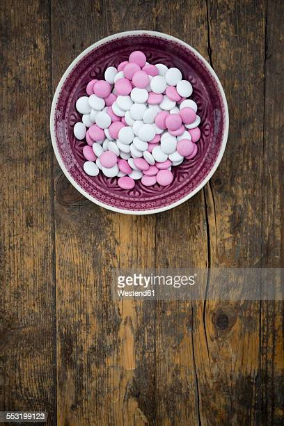 bowl of pink and white chocolate buttons on wood - bowl of candy stock photos and pictures