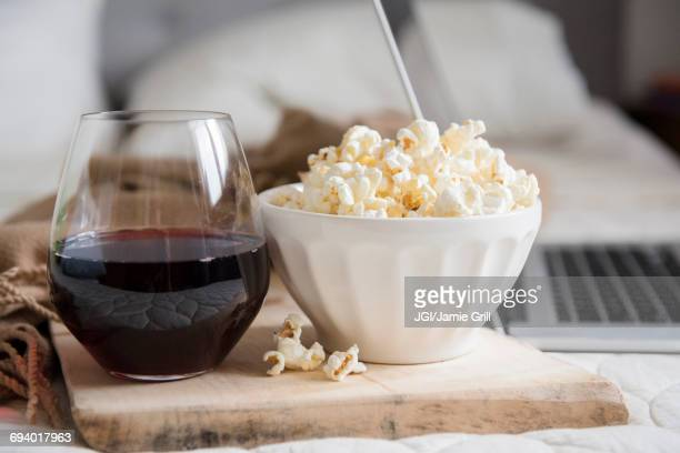bowl of popcorn and glass of wine near laptop - night in stock pictures, royalty-free photos & images