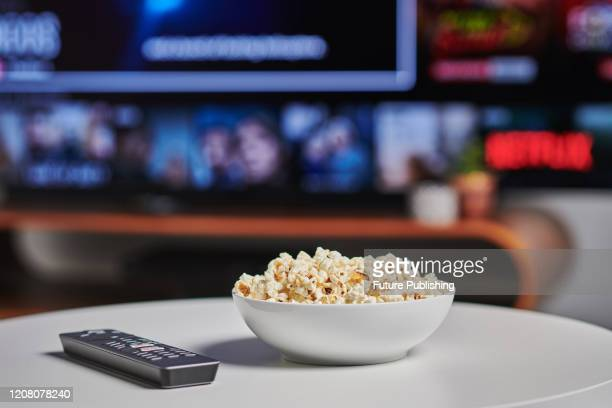 Bowl of popcorn and TV remote control on a coffee table, with Netflix streaming on a television in the background, taken on March 6, 2020.