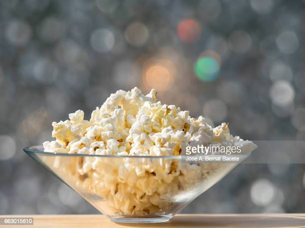 bowl of popcorn, on a wooden table lit by sunlight - frescura ストックフォトと画像