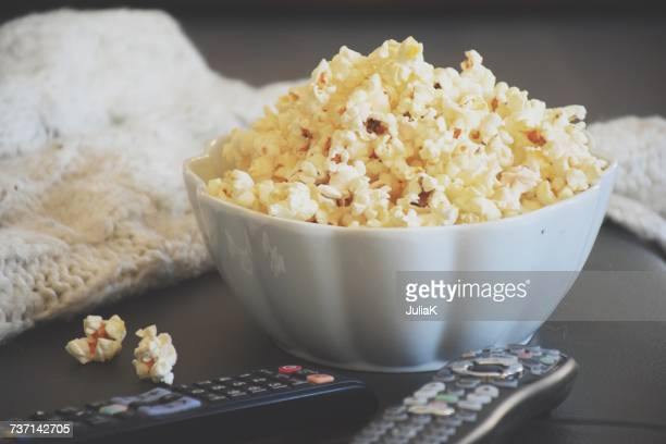 A bowl of popcorn with TV remote controls