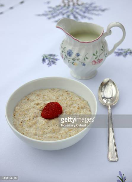 bowl of porridge oats and milk jug - rolled oats stock photos and pictures