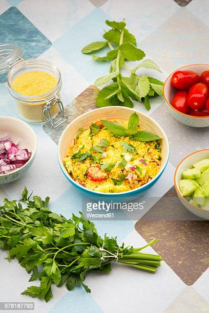 bowl of prepared couscous salad and ingredients - flat leaf parsley stock photos and pictures