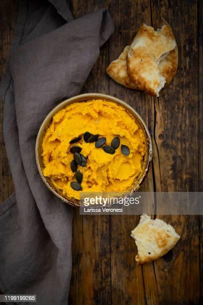 bowl of pumpkin hummus - larissa veronesi stock-fotos und bilder