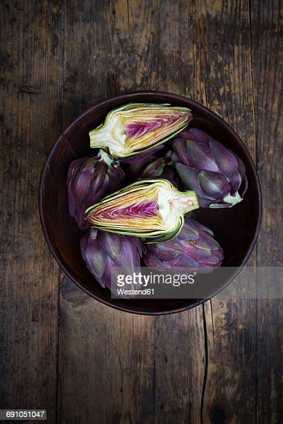 Bowl of purple organic artichokes on dark wood