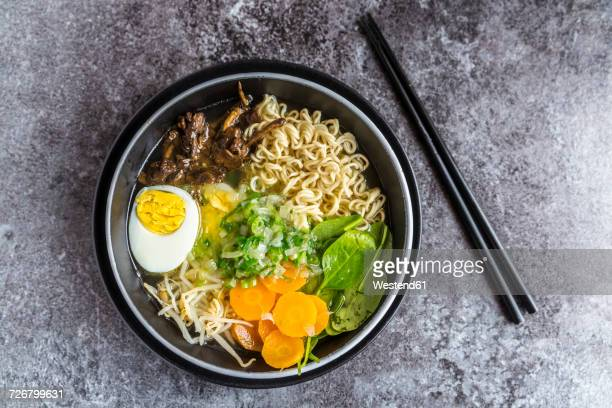 bowl of ramen soup with spinach, carrot, boiled egg, bamboo sprouts and mushrooms - ramen noodles stock pictures, royalty-free photos & images