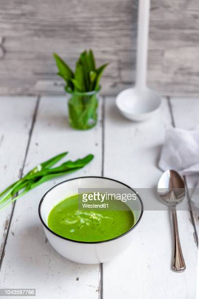 bowl of ramson soup garnished with cream - soup bowl stock pictures, royalty-free photos & images